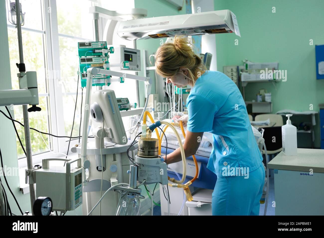 En la unidad de cuidados intensivos. Enfermera parada cerca de la cama del hospital con el bebé preparándolo para el tratamiento. Centro Cardíaco Para Niños.Mayo De 18,2018. Kiev, Ucrania Foto de stock