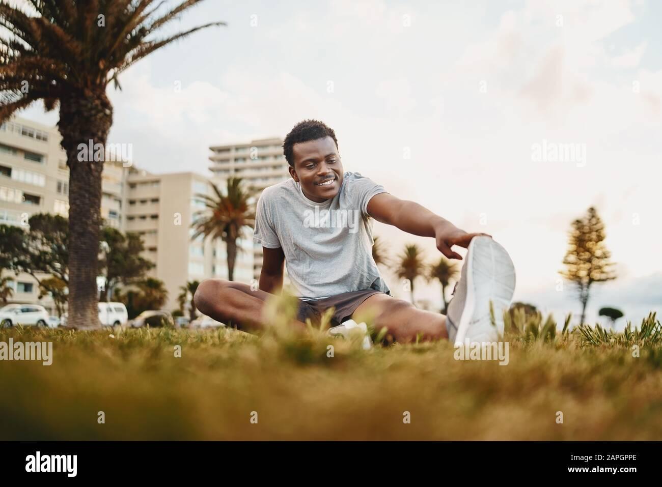 Retrato sonriente de un joven atleta sentado en hierba verde haciendo ejercicio de estiramiento en el parque Foto de stock