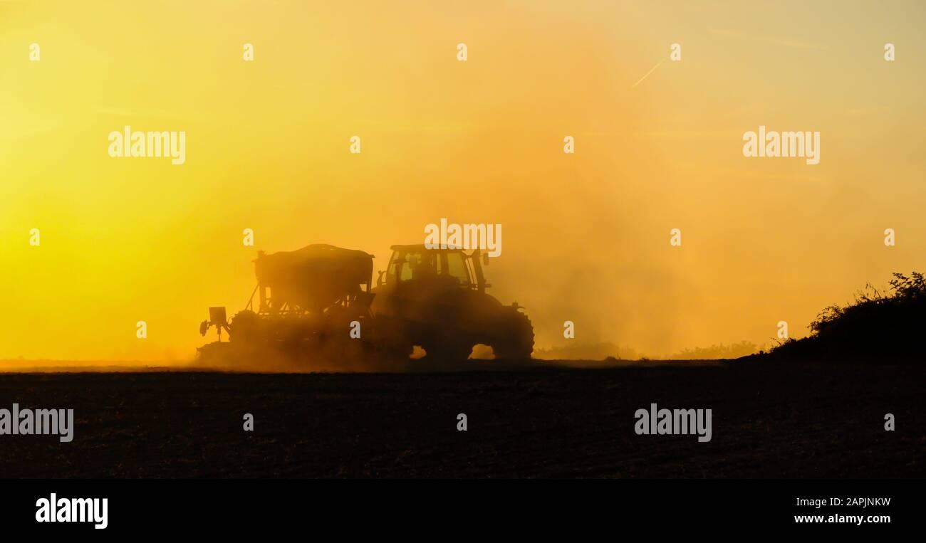Silueta de un tractor sembrando semillas en un campo en una nube de polvo contra el fondo de la puesta de sol. Foto de stock