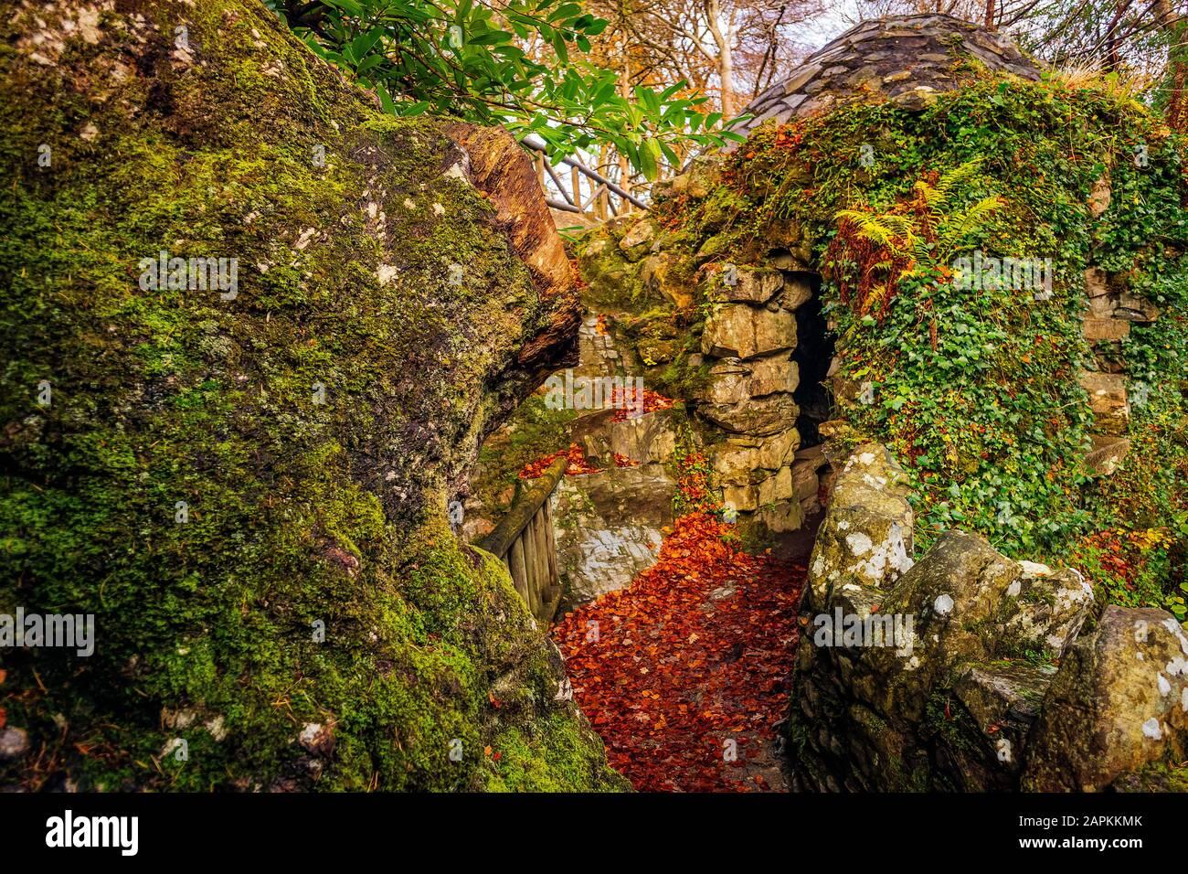 Piedra antigua ruina de cabaña con rocas verdes de musgo en el Parque Forestal Tollymore en otoño, Newcastle, County Down, Irlanda del Norte Foto de stock