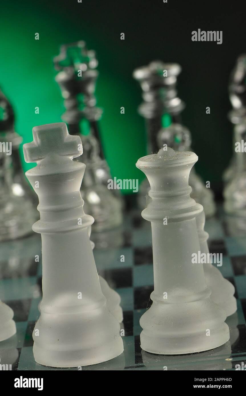 Piezas de vidrio de ajedrez en el tablero de ajedrez Foto de stock