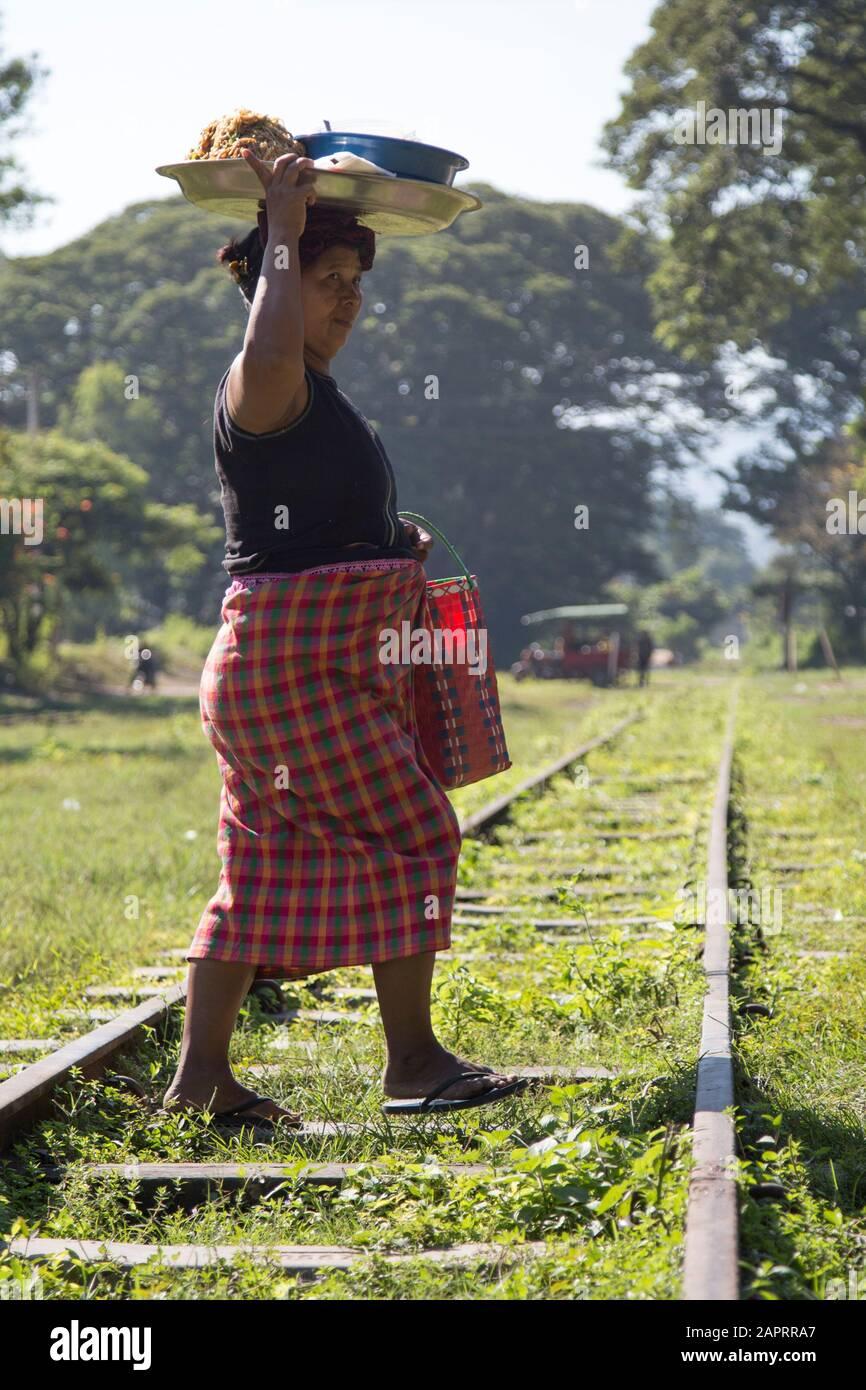 Mujer birmana llevando bandeja de comida sobre su cabeza, cruzando un ferrocarril Foto de stock