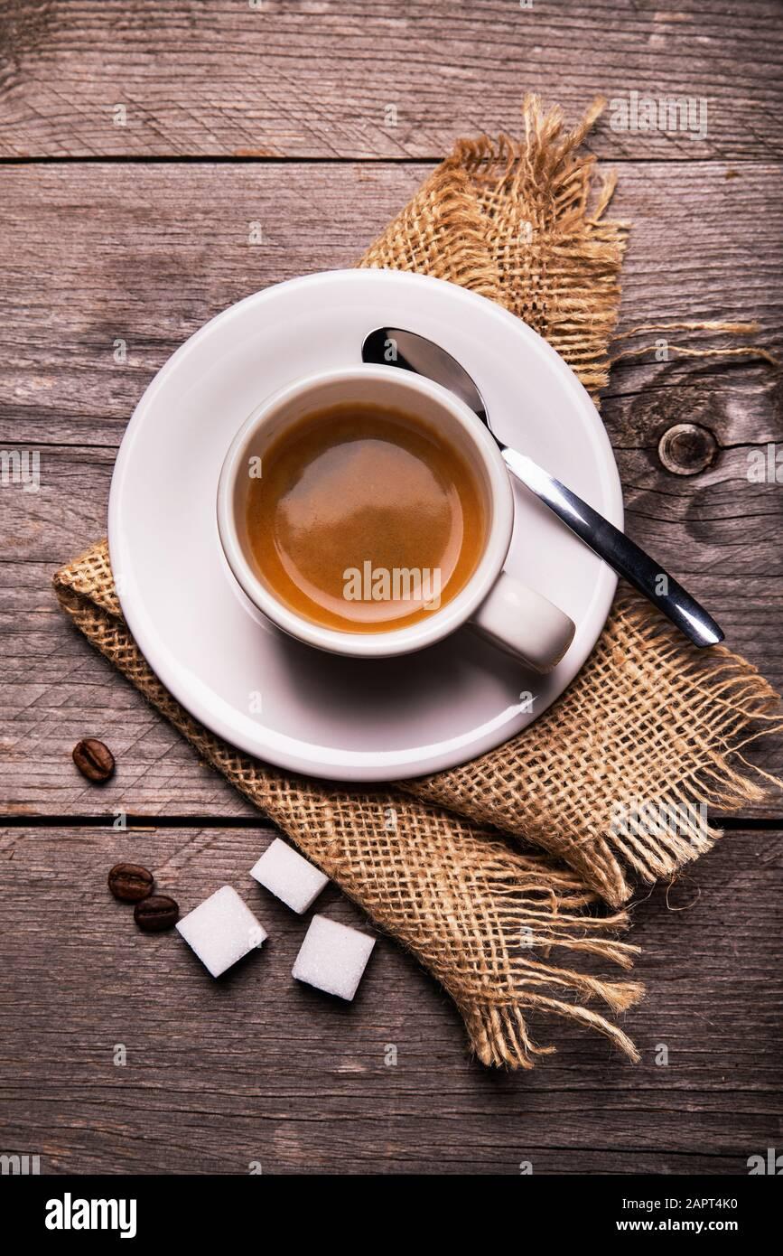 en la mesa rústica de madera, en primer plano, con vistas desde la parte superior, una taza de café espresso cremoso. Composición vertical Foto de stock