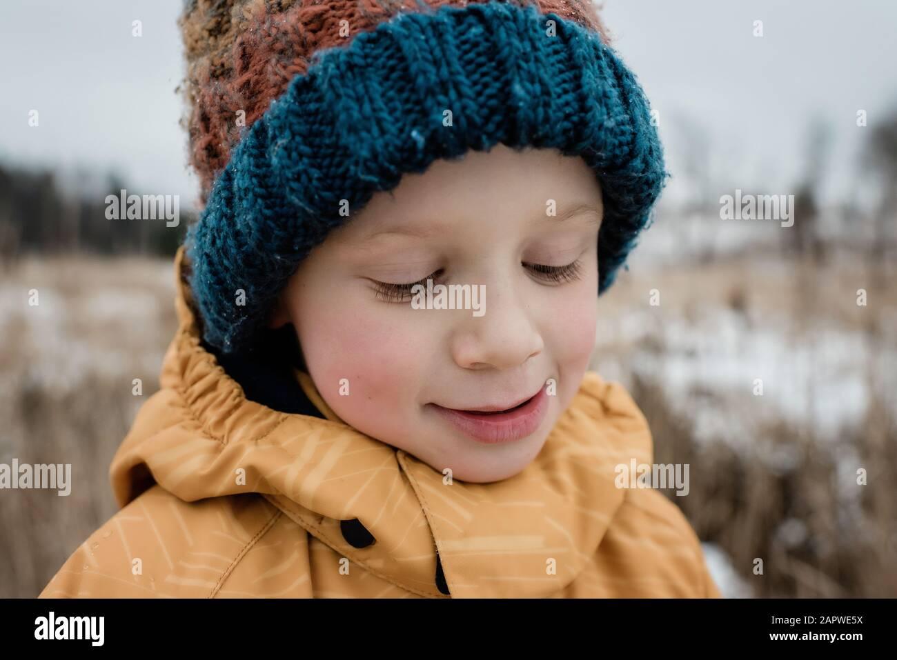 primer plano de un niño mirando hacia abajo sonriendo mientras juega fuera Foto de stock