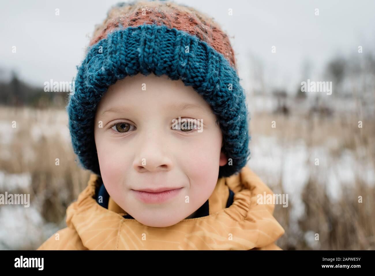 retrato de un niño mirando mientras juega fuera en invierno Foto de stock