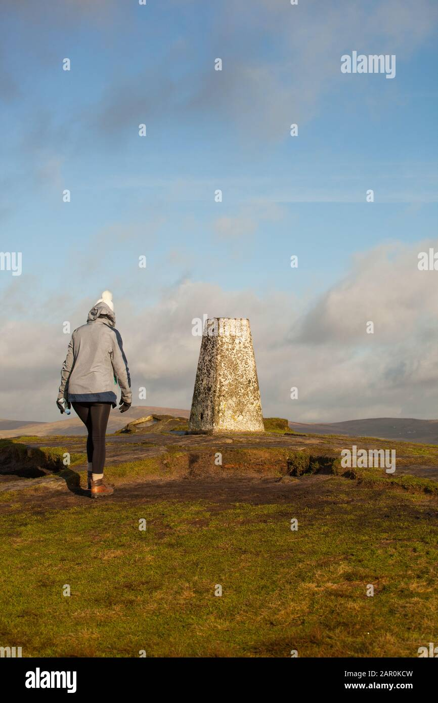 Mujer caminando hasta el punto de triangulación punto trig en la colina de Shutlingsloe en el distrito de los picos ingleses Foto de stock