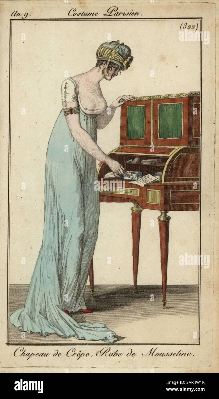 Mujer de moda o Esterveilleuse en una escritoire, 1801. Lleva un sombrero de crepé atado bajo la barbilla, un vestido de muselina de corte bajo que revela los pezones, con mangas cortas. 18 o 23 de agosto de 1801. Introducción de Crêpe. Robe de Mousseline.Grabado de coperplato de color manual del Journal des Modes et Dames de Pierre de la Mesangere, París, 1801. Las ilustraciones en el volumen 4 fueron de Carle Vernet, Bosio, Dutailly y Philibert Louis Debucourt. Foto de stock
