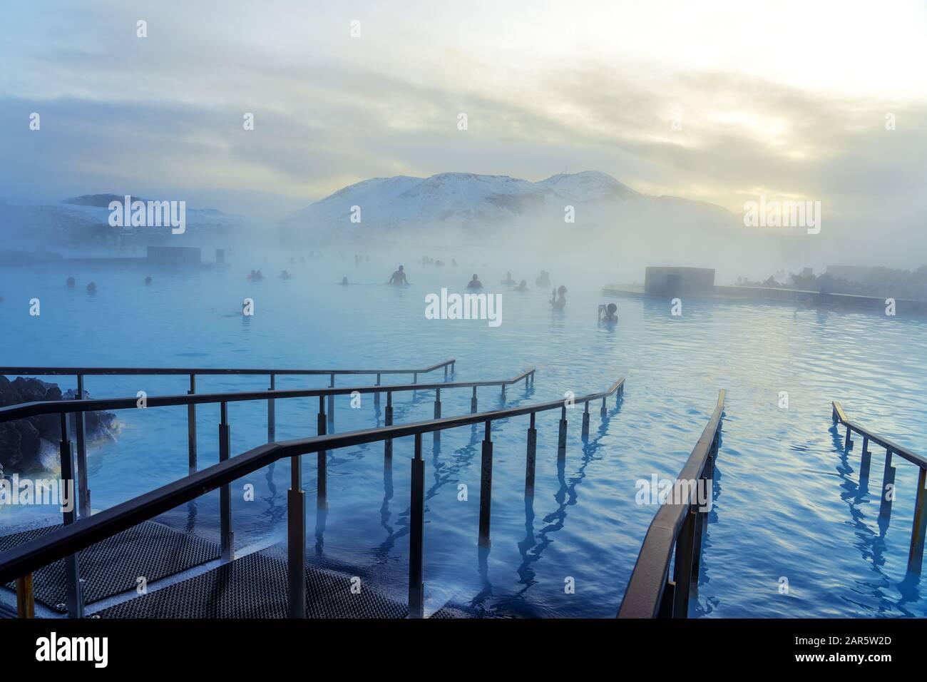 Laguna azul junto a Reykjavik con gente bañándose en esta fuente termal natural. Foto de stock