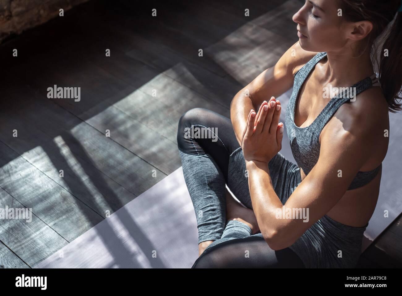 Calma ajuste mujer sana sentarse en la pose del loto hacer yoga medita interior, vista del primer plano Foto de stock