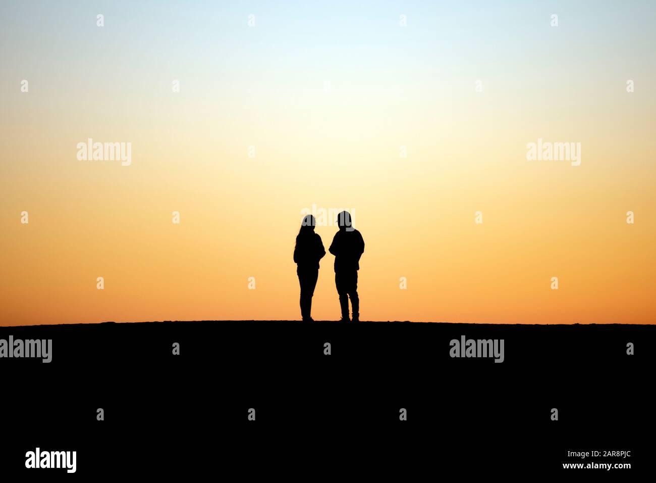 Dos personas siluetas contra el cielo crepuscular se encuentran juntas lado a lado Foto de stock