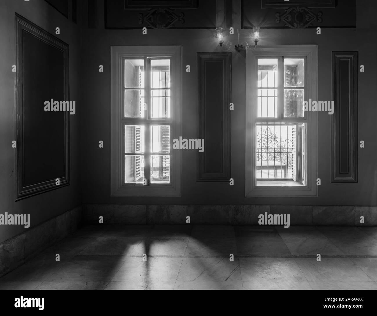 Blanco y negro captura de alto contraste de dos ventanas estrechas, revelando una fuerte luz en la habitación oscura con suelo de mármol blanco azulejado Foto de stock