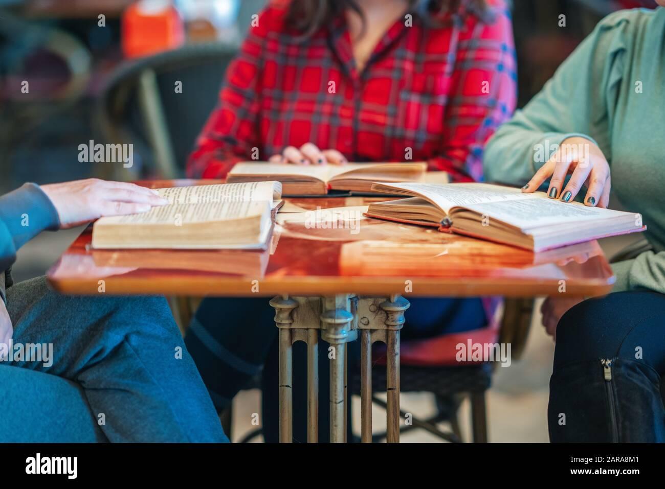 Tres mujeres intelectuales sentadas y leyendo libros en la biblioteca o cafetería Foto de stock