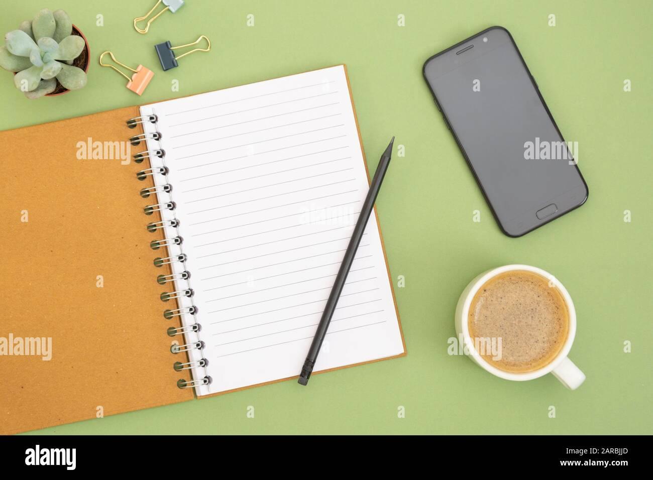 Cuaderno en blanco con página vacía, taza de café y mano sosteniendo un lápiz. Tablero, espacio de trabajo sobre fondo verde. Diseño plano creativo. Foto de stock