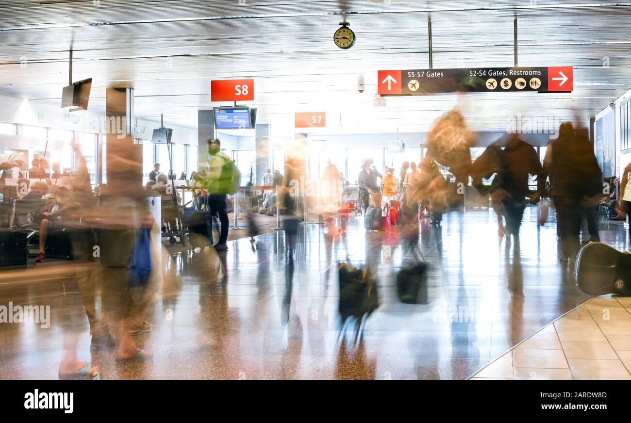 Pasajeros de líneas aéreas en un aeropuerto internacional dentro de una terminal muy concurrida. Foto de stock