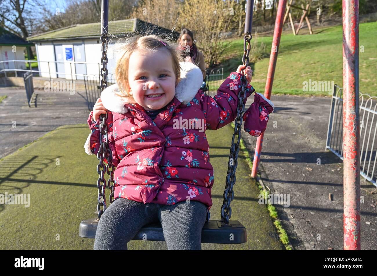 Brighton Reino Unido 28 de enero de 2020 - Isabella de 3 años disfruta de un paseo en los columpios en Queens Park Brighton con su madre empujando en un hermoso día soleado pero frío en Gran Bretaña . Crédito: Simon Dack / Noticias En Vivo De Alamy Foto de stock