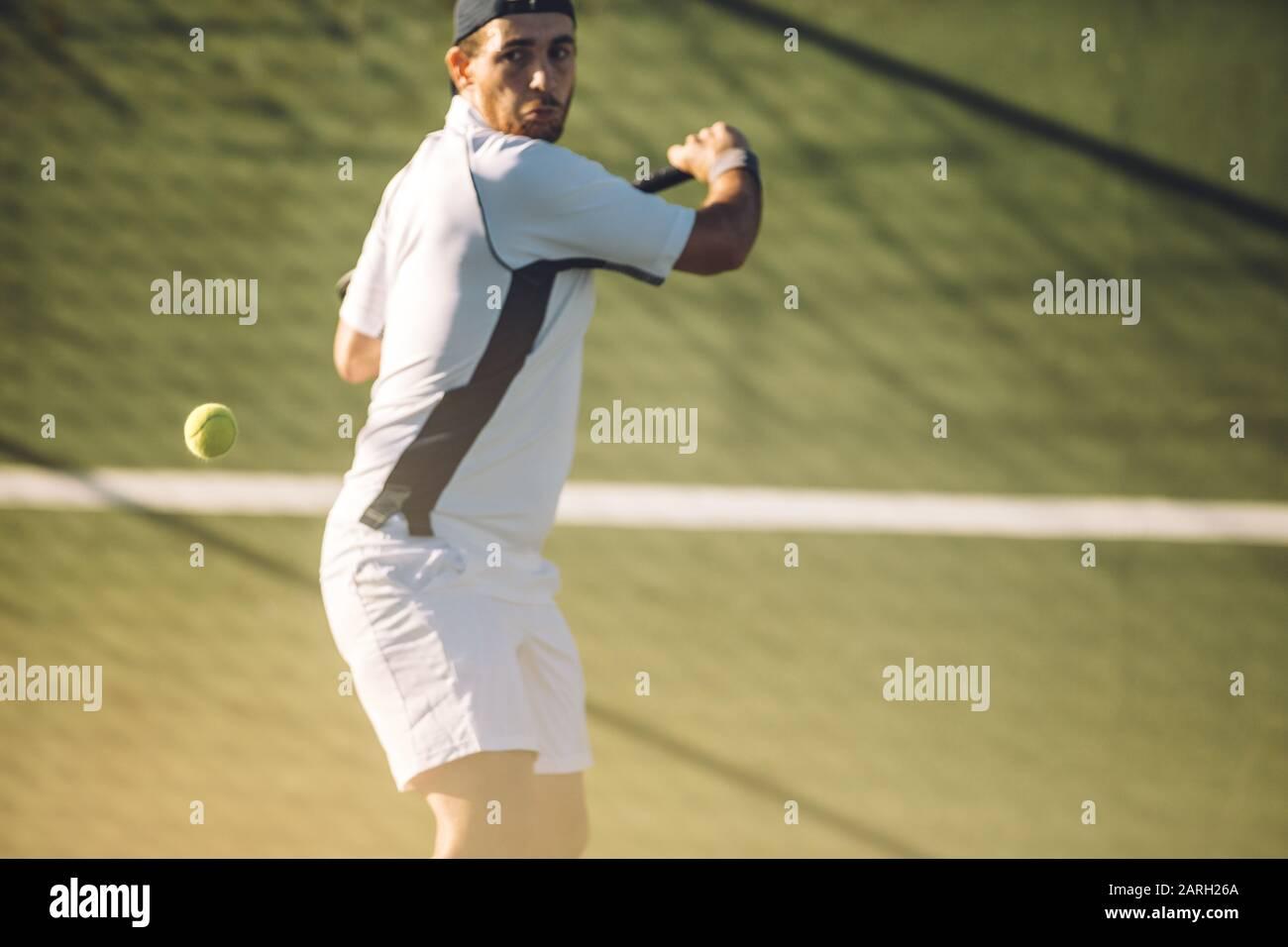 Joven jugador de tenis masculino golpeando una poderosa mano trasera durante un partido. Jugador de tenis jugando al tenis en una pista de tenis. Foto de stock