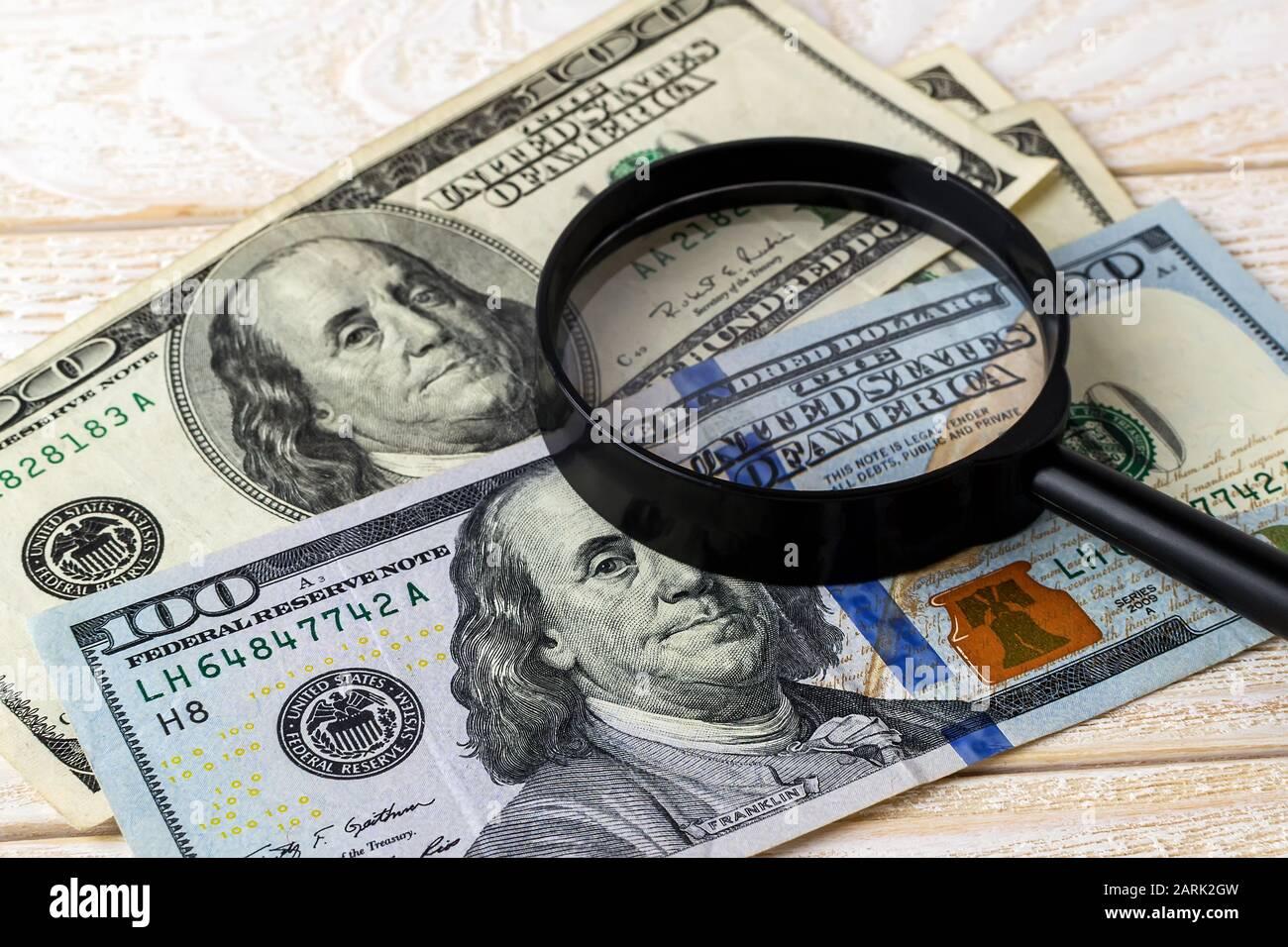 Lupa sobre billetes nuevos y viejos en una superficie de madera blanca. Compruebe la autenticidad del dinero. Concepto de riqueza, pobreza y falsificación de dinero Foto de stock