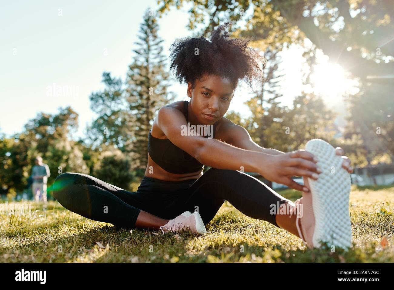 Retrato de una mujer joven afroamericana determinada sentada en hierba verde por la mañana, la luz del sol estirando las piernas mirando a la cámara Foto de stock