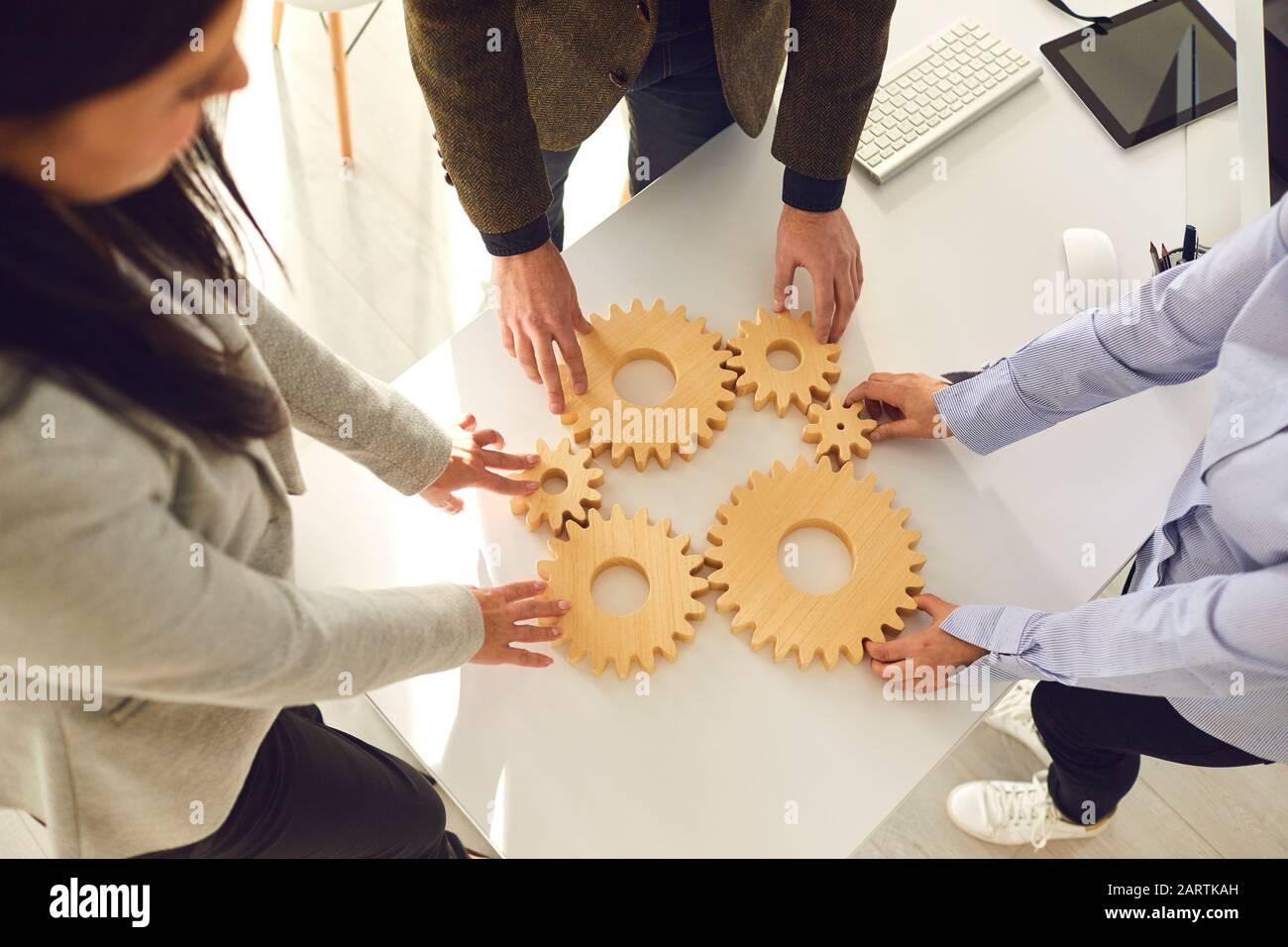 Un grupo de gente de negocios sostiene ruedas de madera con dientes en sus manos en una mesa blanca de oficina. Foto de stock