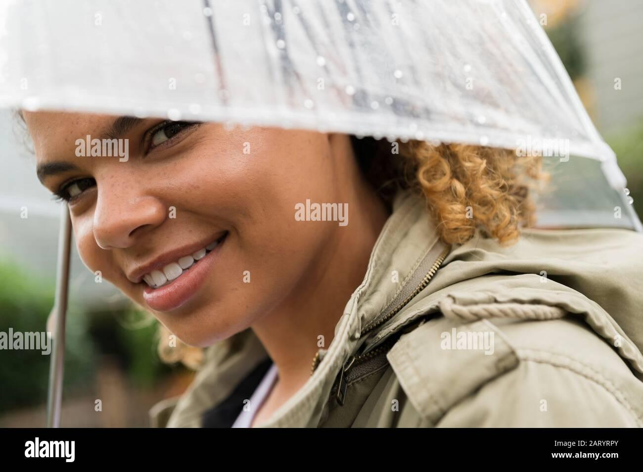 Mujer sonriente bajo paraguas mojado Foto de stock