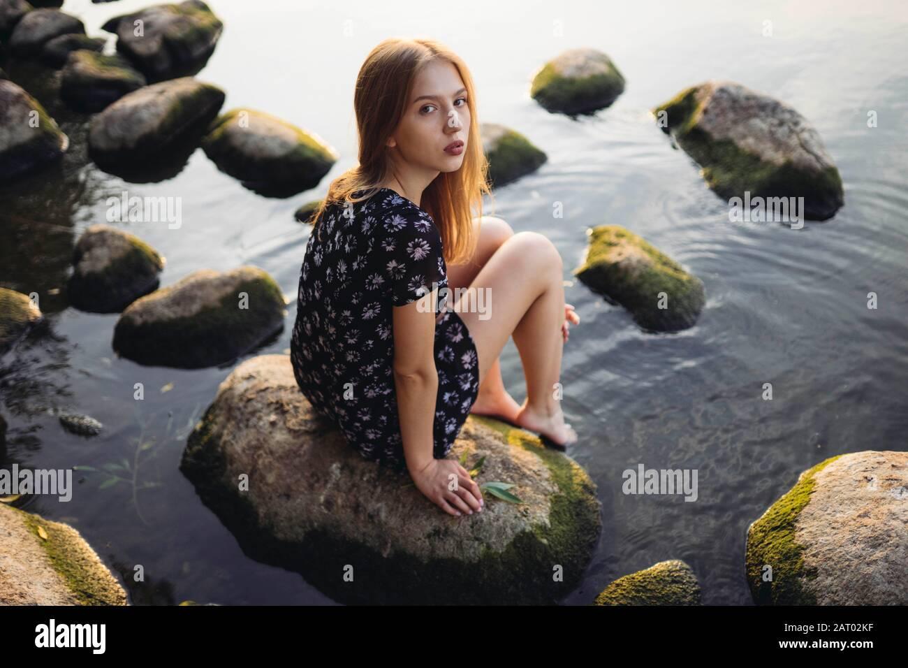 Mujer con vestido negro sentado en roca en el mar Foto de stock