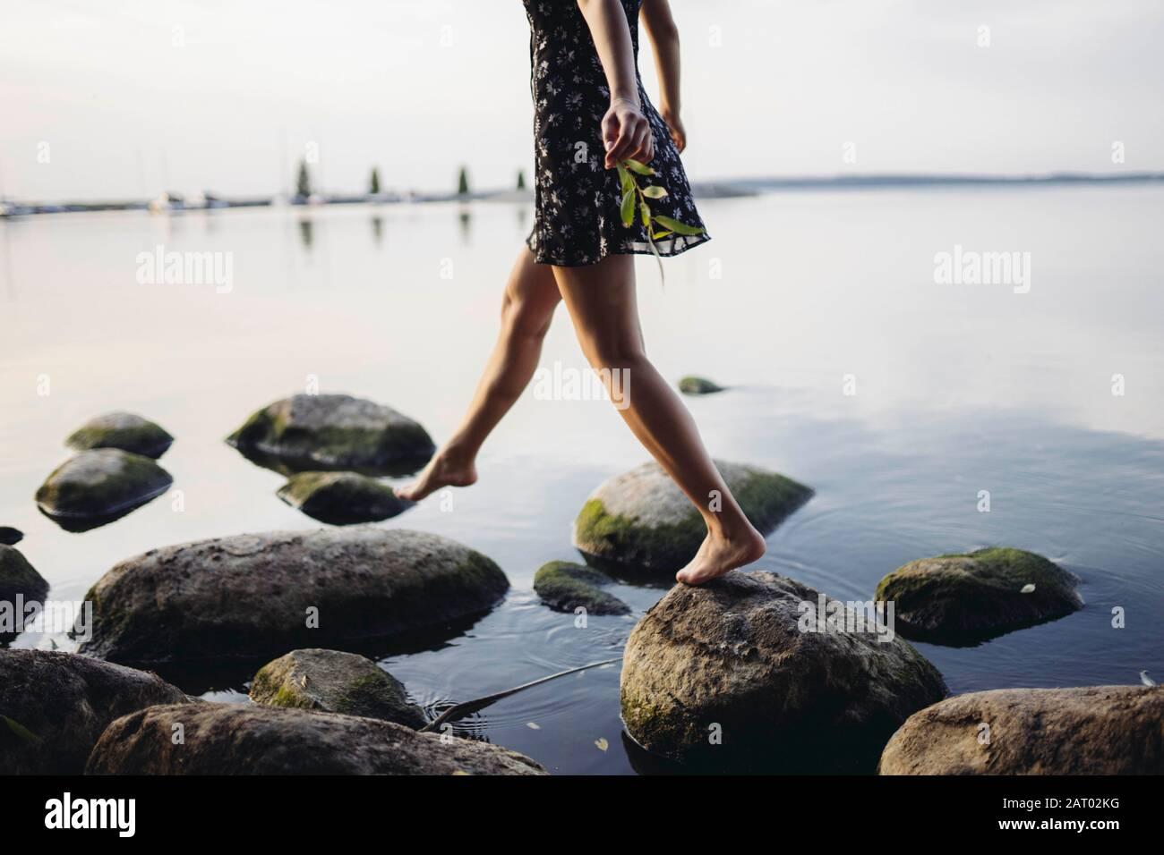 Mujer descalza caminando sobre rocas en el mar Foto de stock
