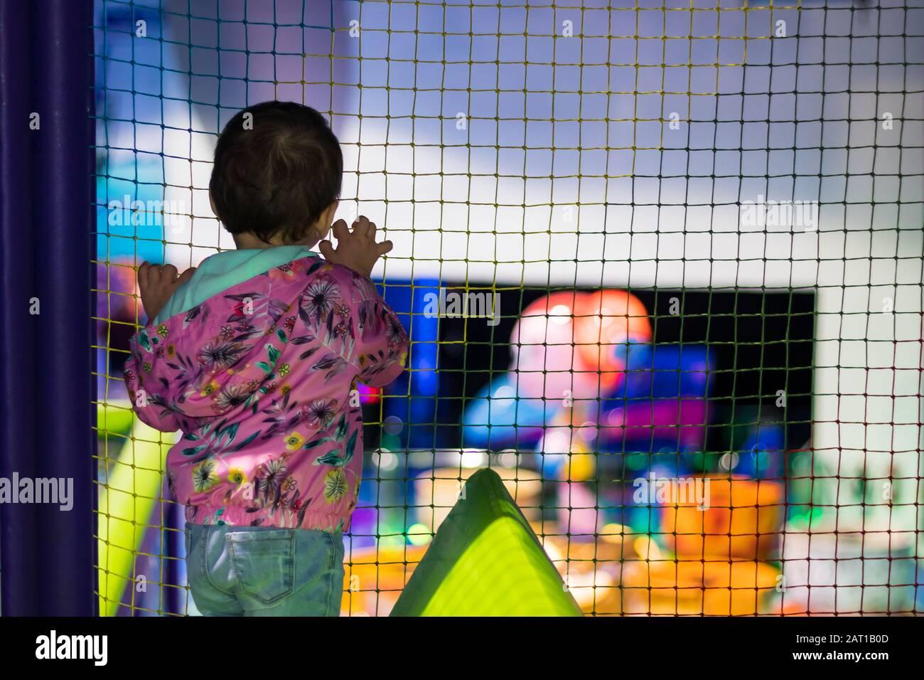 Una linda niña en un parque infantil cubierto en un centro comercial en Dubai, Emiratos Árabes Unidos. Foto de stock
