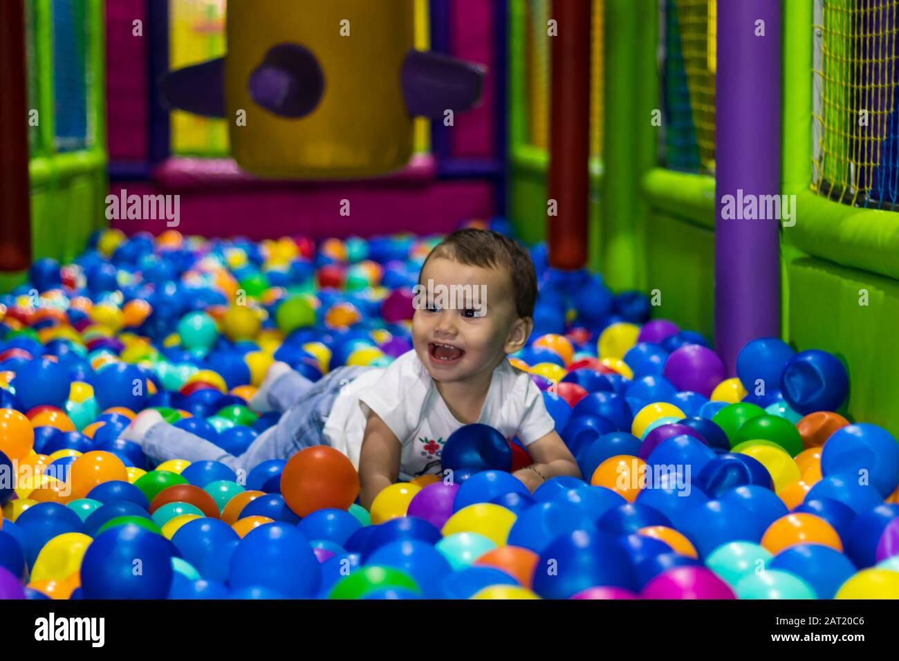 Una chica pequeña linda y feliz riendo y jugando en un patio interior en un centro comercial en Dubai, Emiratos Árabes Unidos. Foto de stock
