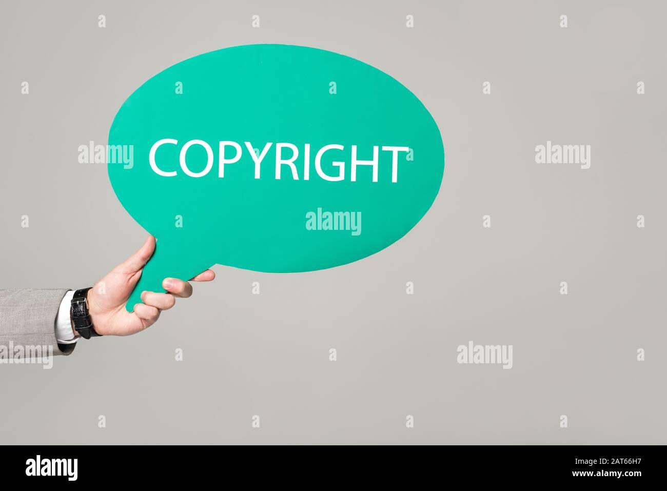 vista recortada de empresario sosteniendo burbuja de pensamiento con inscripción de derechos de autor aislada en gris Foto de stock