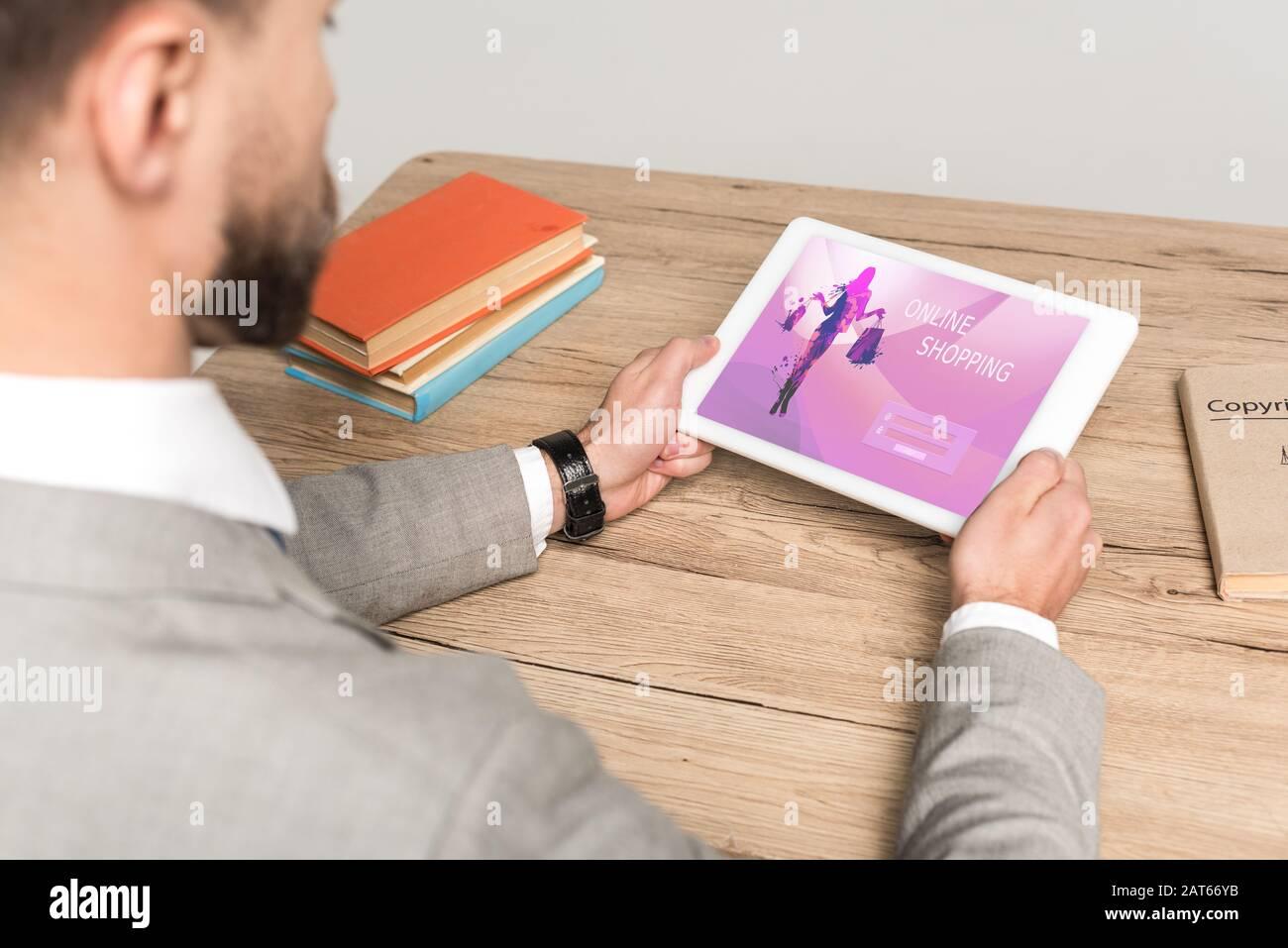 vista recortada de los hombres de negocios con tableta digital con aplicación de compras en línea en pantalla aislada en gris Foto de stock