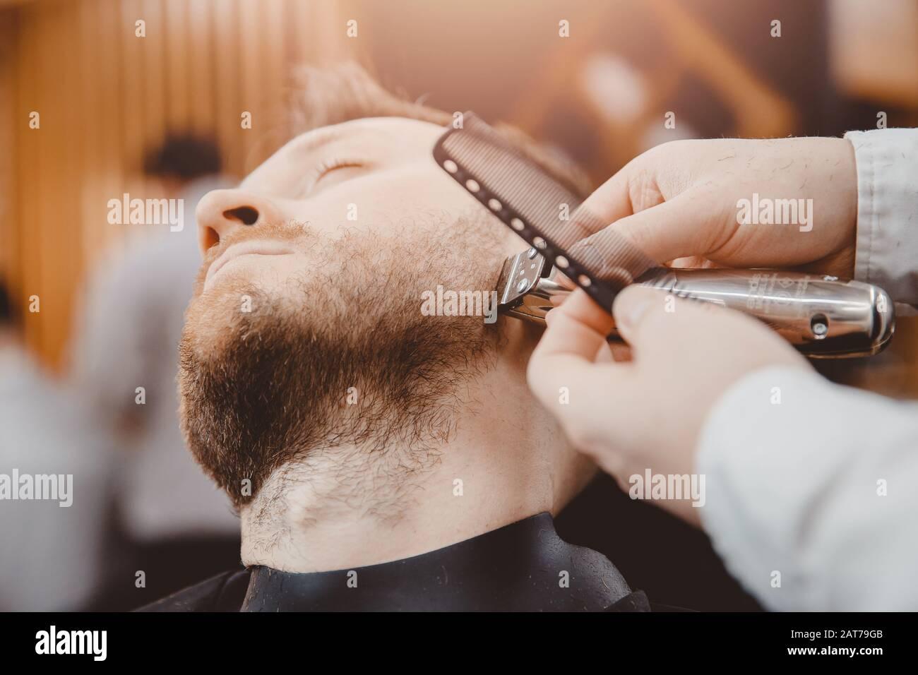Hombre de la clienta de Hipster que visita en la peluquería de peluquería, Vintage tintado marrón Foto de stock
