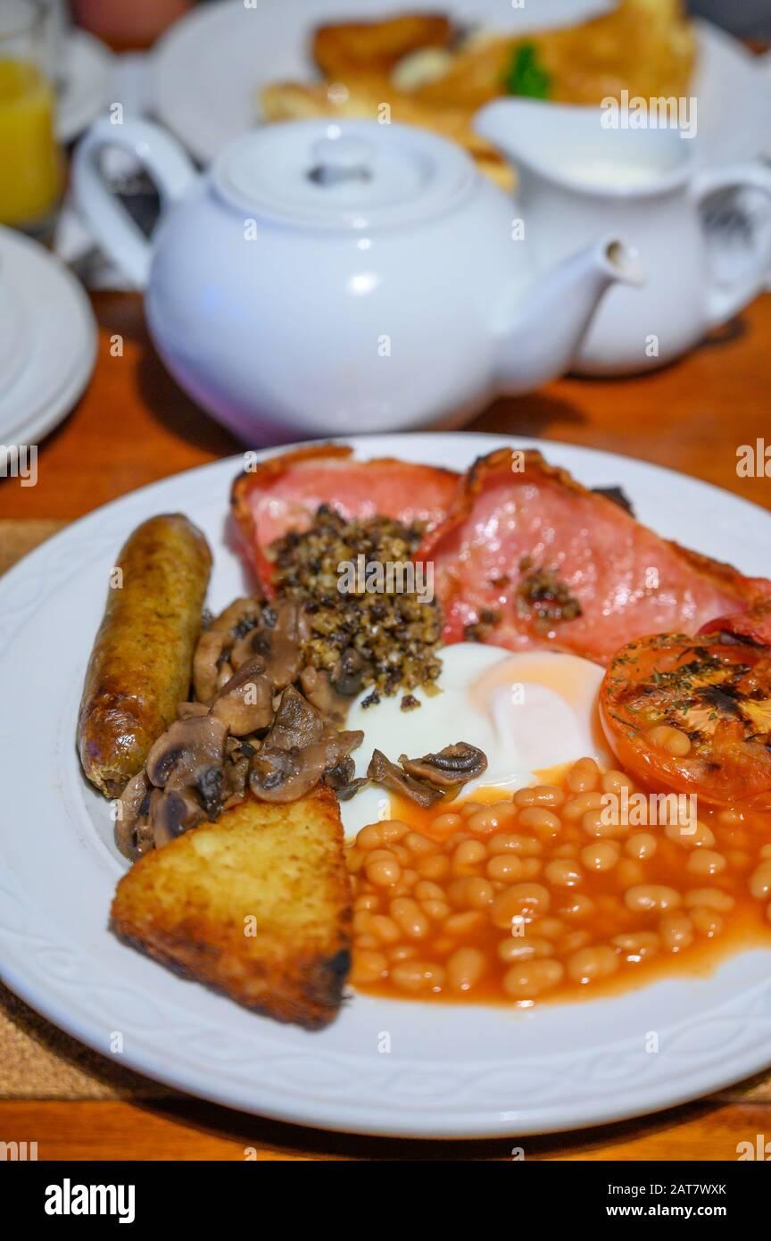 Pizarra blanca con desayuno escocés completo con tocino, huevo frito, frijoles, tomate, salchichas asadas, pudín, croquetas de patata y haggis Foto de stock