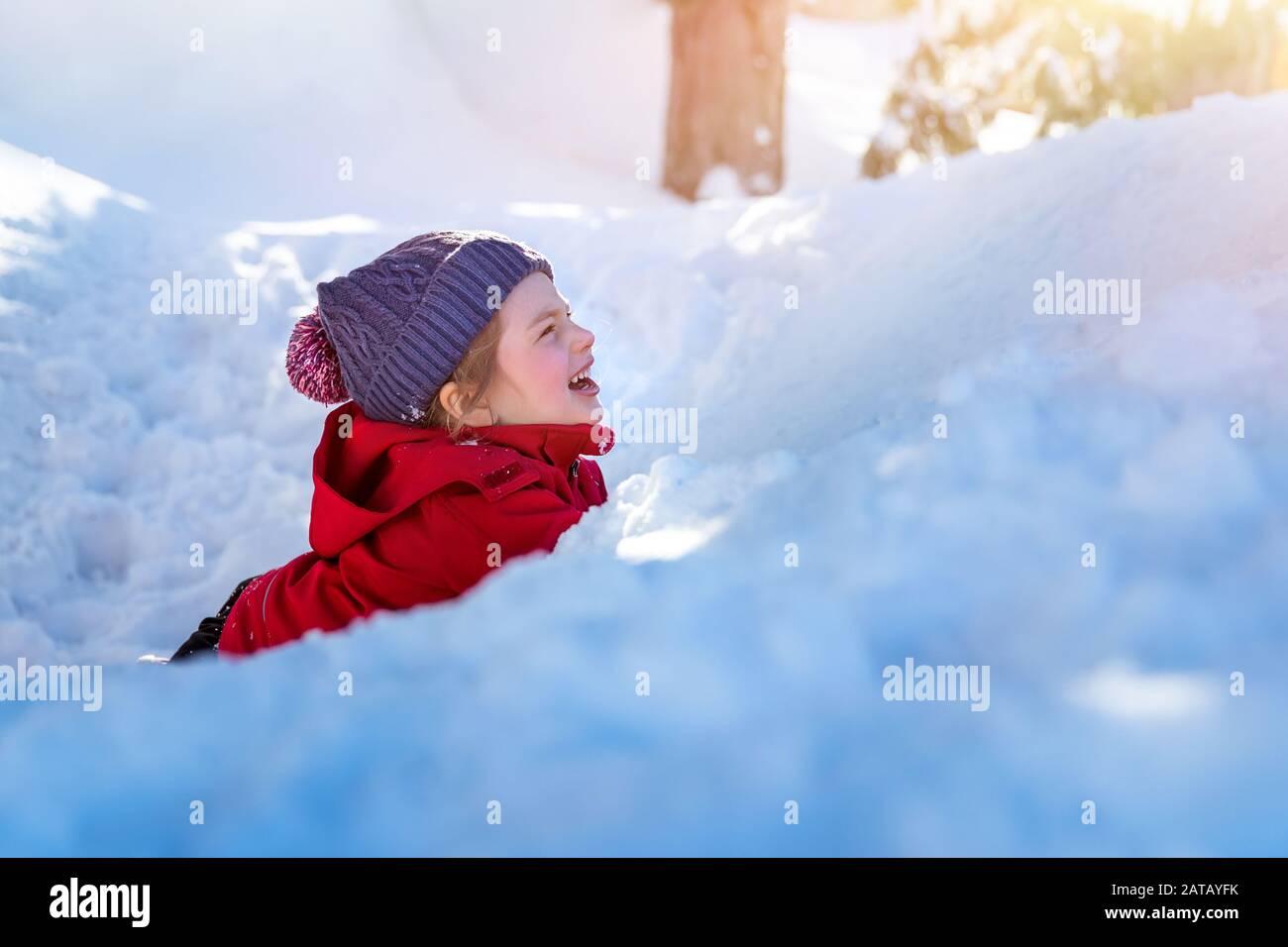 Niño alegre en la nieve, niña encantadora y linda tumbada en la pila de nieve y riendo, disfrutando de las vacaciones de invierno, feliz infancia sin preocupaciones Foto de stock