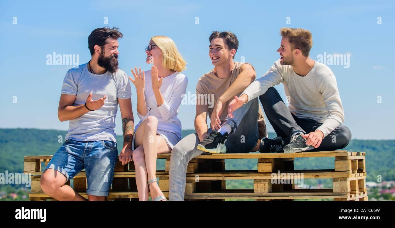 Descanso de verano. Pasar tiempo con amigos. Vacaciones de verano. Gente alegre que se comunica. Hombres y mujeres hablando de naturaleza de fondo. Jóvenes relajados. Ocio de verano. Concepto sin preocupaciones. Pase el rato juntos. Foto de stock