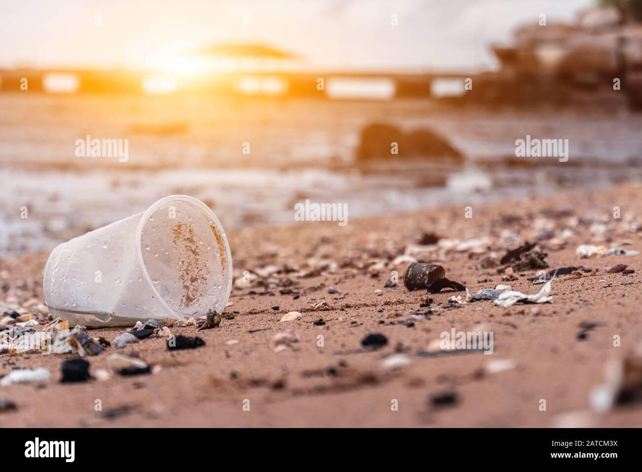 Vasos de plástico y basura en la playa de arena. Conciencia Medioambiental Y Plástica. Concepto Del Día Mundial Del Medio Ambiente. Salva la vida de la tierra. Foto de stock