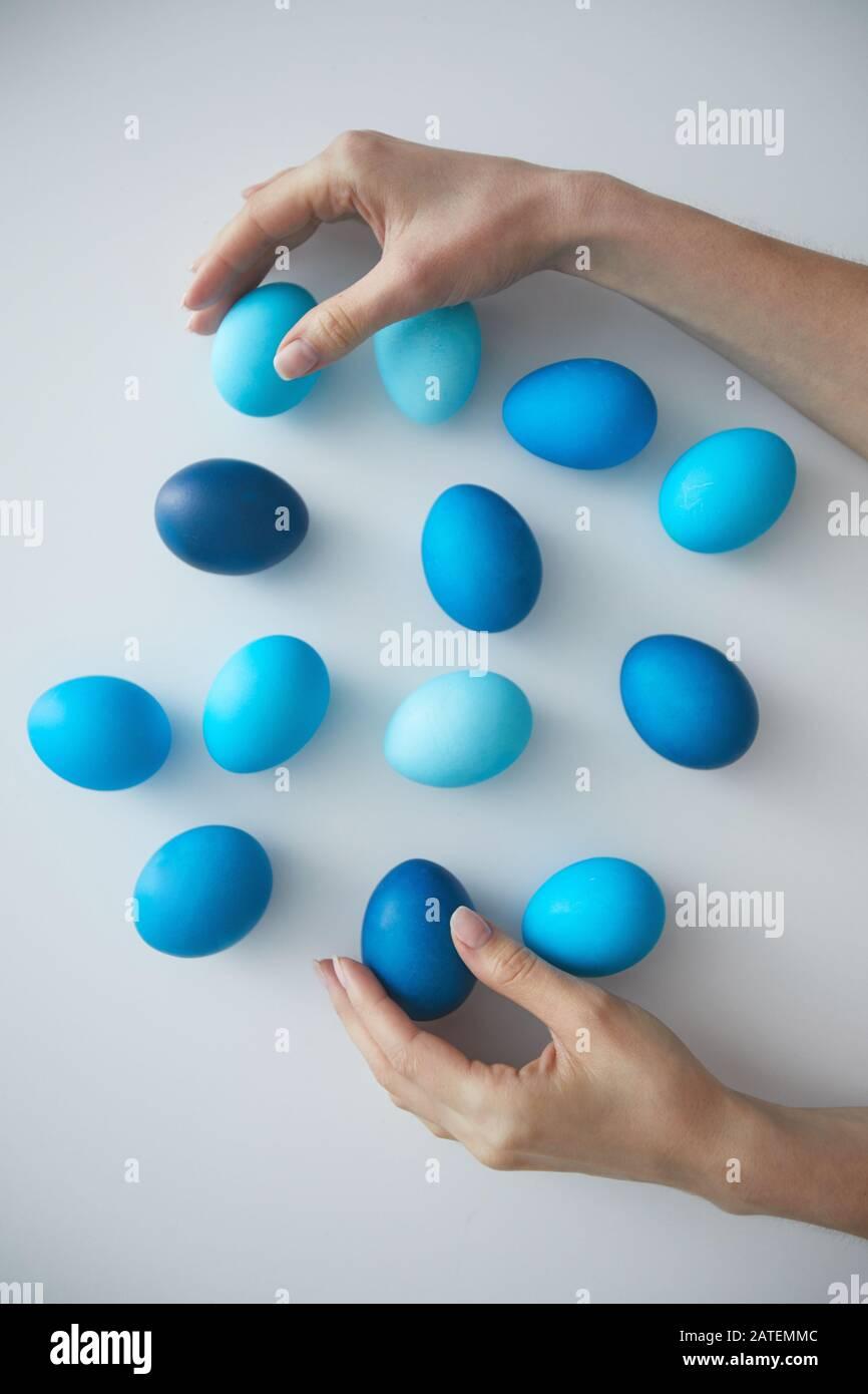 Sobre vista fondo hembra mano arreglando composición de huevos de Pascua pintados de azul en blanco, espacio de copia Foto de stock