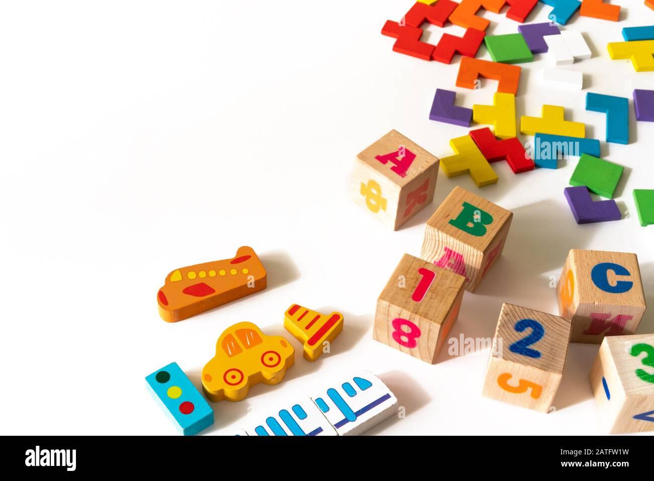 Coloridos juguetes para niños pequeños sobre fondo blanco. Marco de desarrollo de bloques de colores, coches y avión, rompecabezas. Vista superior. Capa plana. Espacio de copia para texto Foto de stock