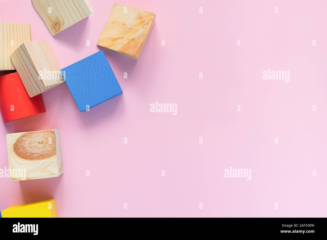 Juguetes de madera para niños sobre un concepto de fondo rosa cero al oeste. Marco de cubos de colores en desarrollo. Espacio de copia. Diseño plano de vista superior. Foto de stock
