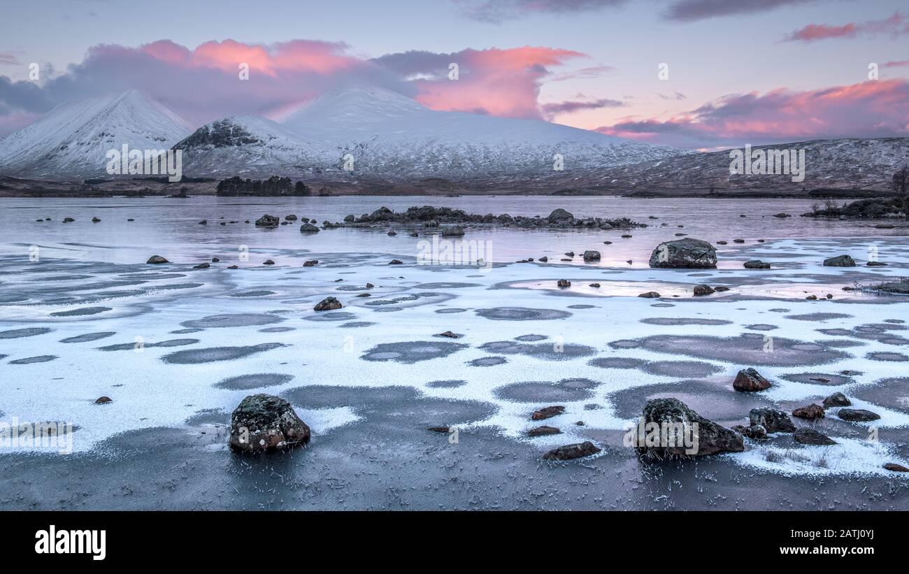 Amanecer sobre un Lochan na h-achlaise congelado en Rannoch Moor cerca de la entrada a Glencoe en las tierras altas de Escocia Foto de stock