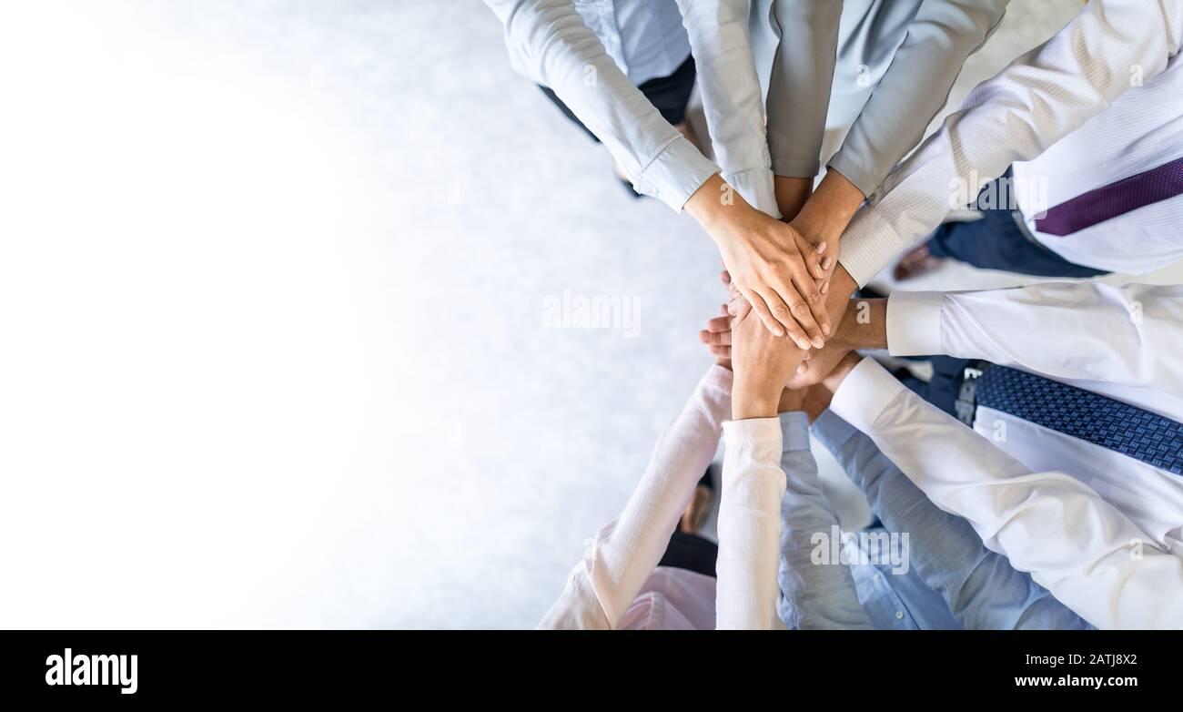Cerrar vista superior de jóvenes empresarios poniendo sus manos juntas. Pila de manos. Concepto de la unidad y el trabajo en equipo. Foto de stock