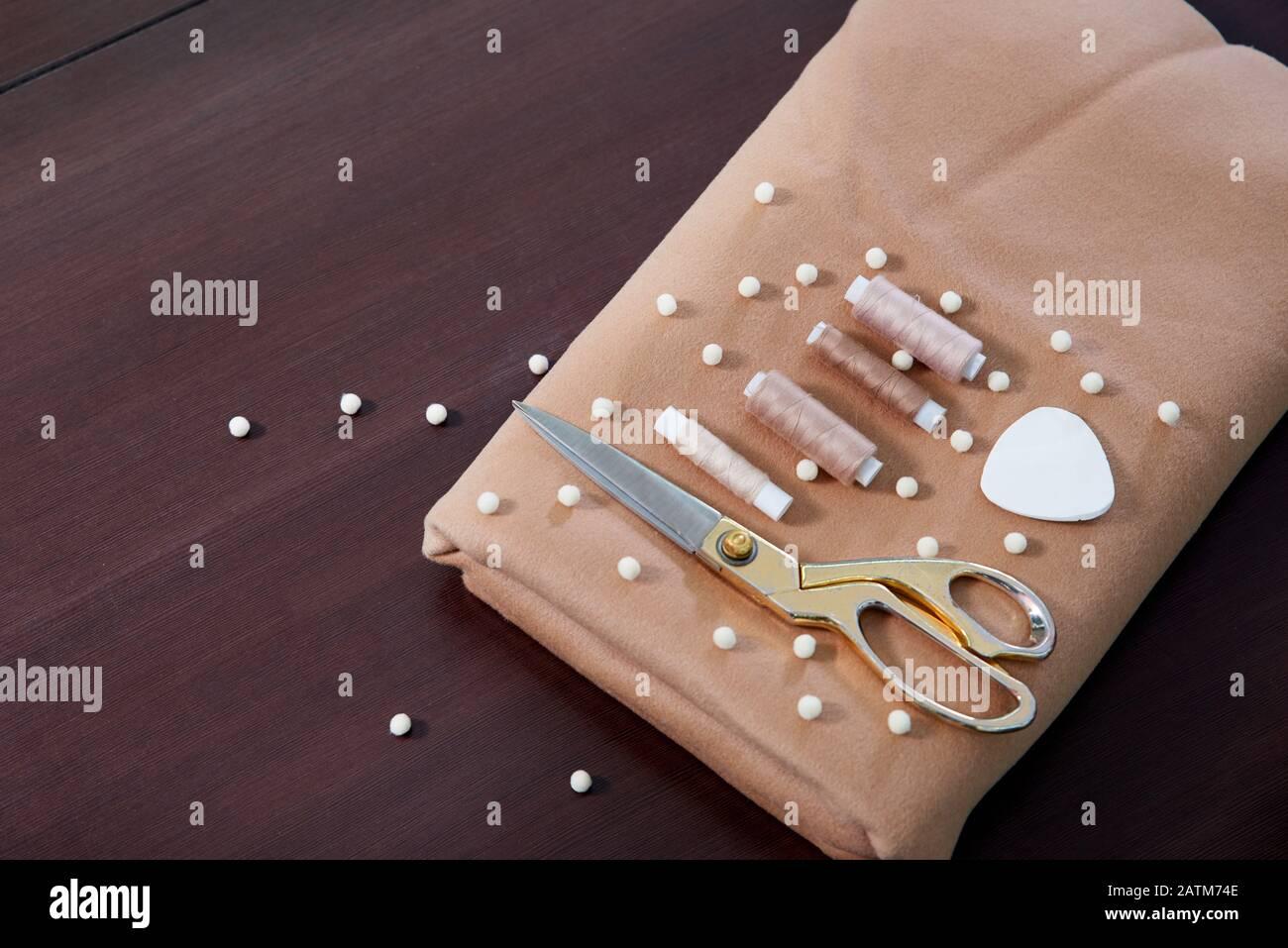Grupo de objetos de costura tumbados sobre fondo negro de pizarra. Fondo horizontal para anuncios o embalajes. Foto de stock