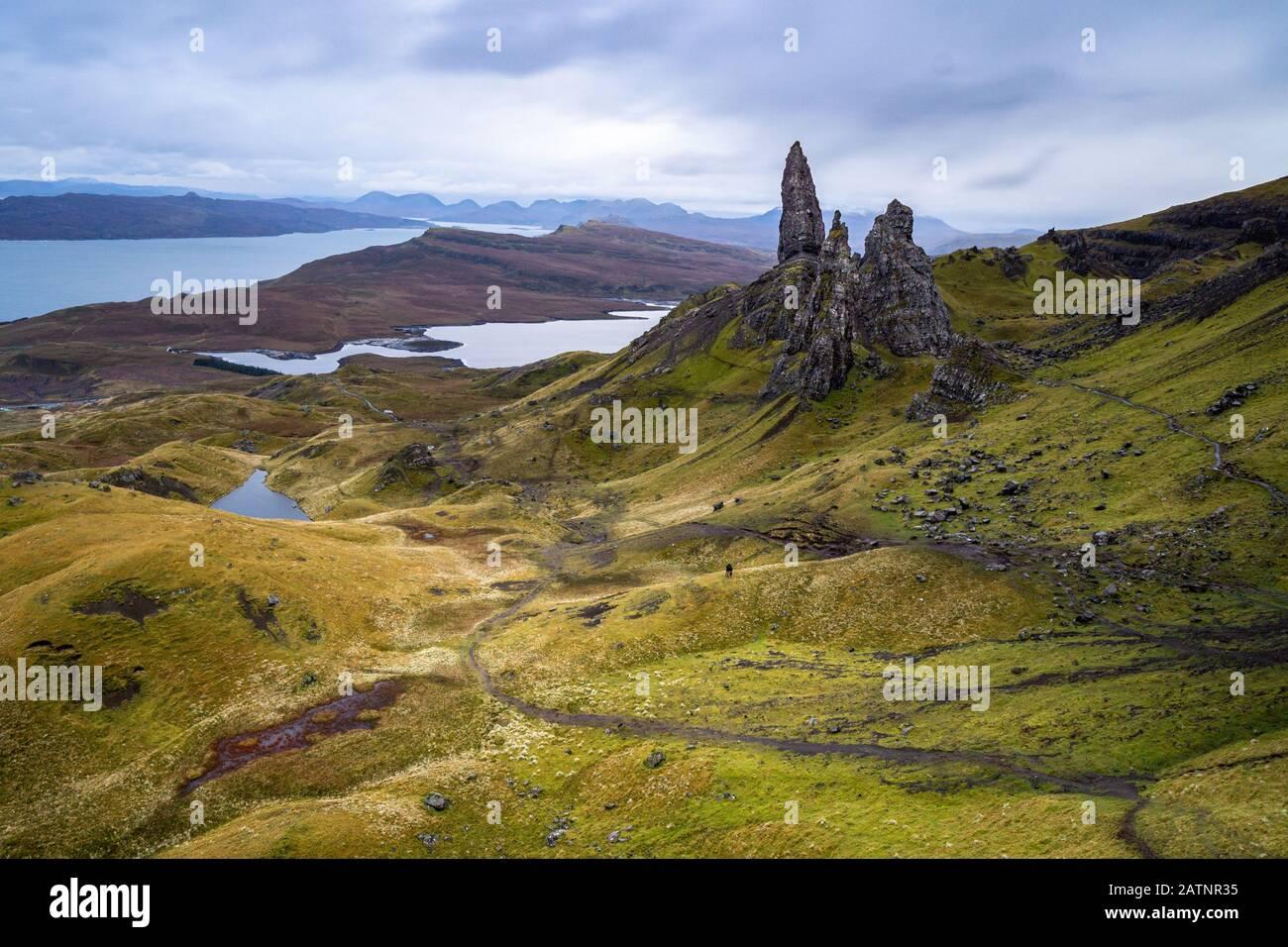 El famoso Viejo Hombre de Storr en Skye es simplemente formidable. La silueta de las dos personas en el centro de la imagen muestra la magnitud de las rocas. Foto de stock