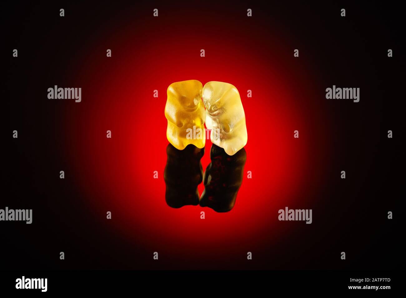 Dos osos gomosos bajo el foco rojo. Concepto de amistad, amor o intimidad Foto de stock