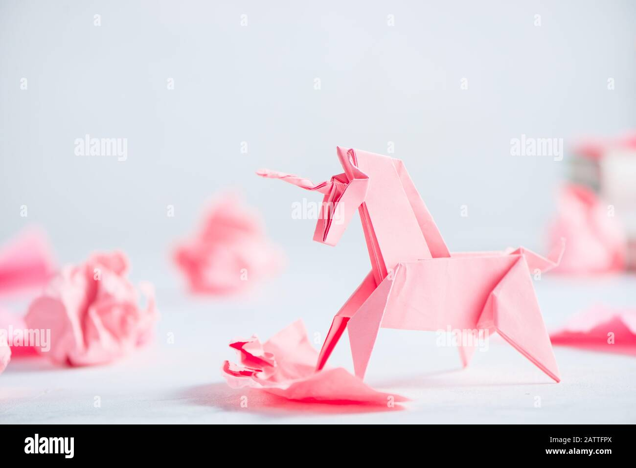 Unicornio de origami rosa con bolas de papel arrugadas. El proceso creativo es la escritura, el fondo ligero Foto de stock
