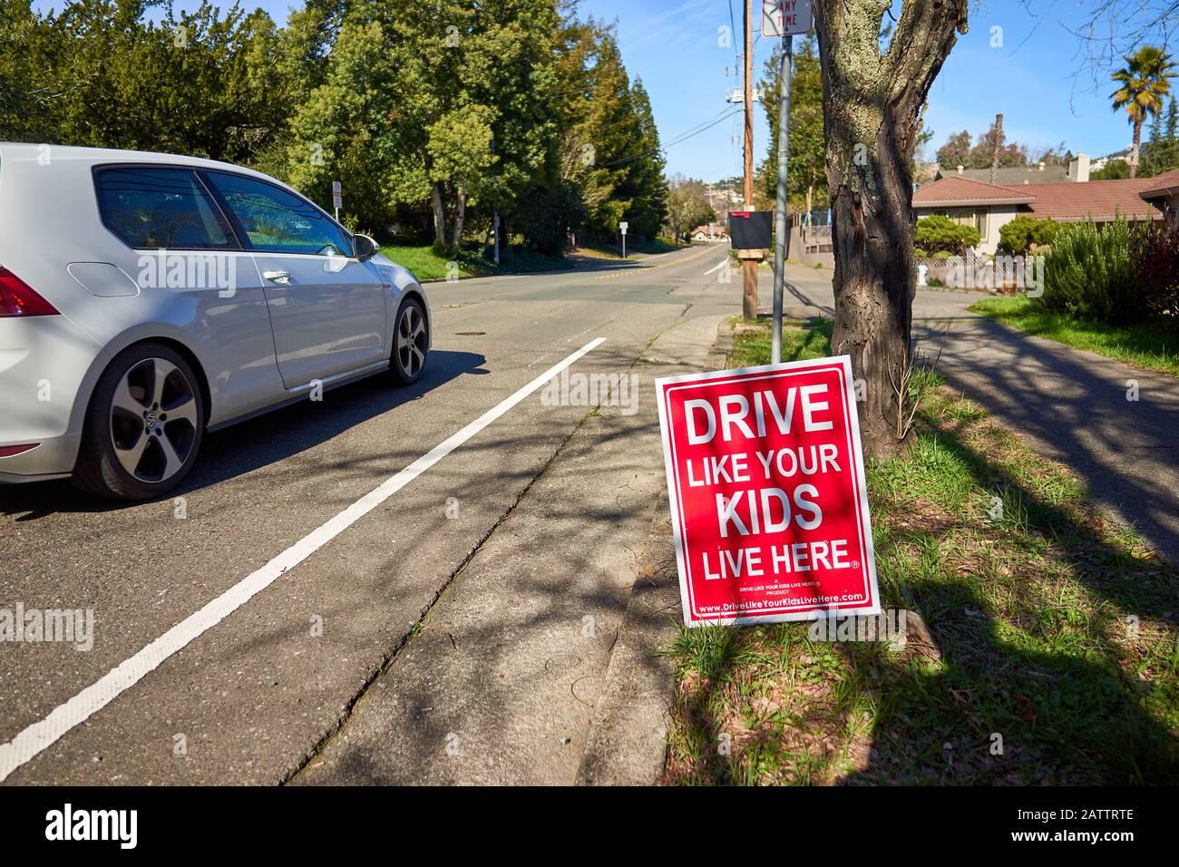 Una señal de carretera alertando a los conductores lee CONDUCIR COMO SUS HIJOS VIVEN AQUÍ mientras un coche blanco pasa por una calle en Santa Rosa, California. Foto de stock