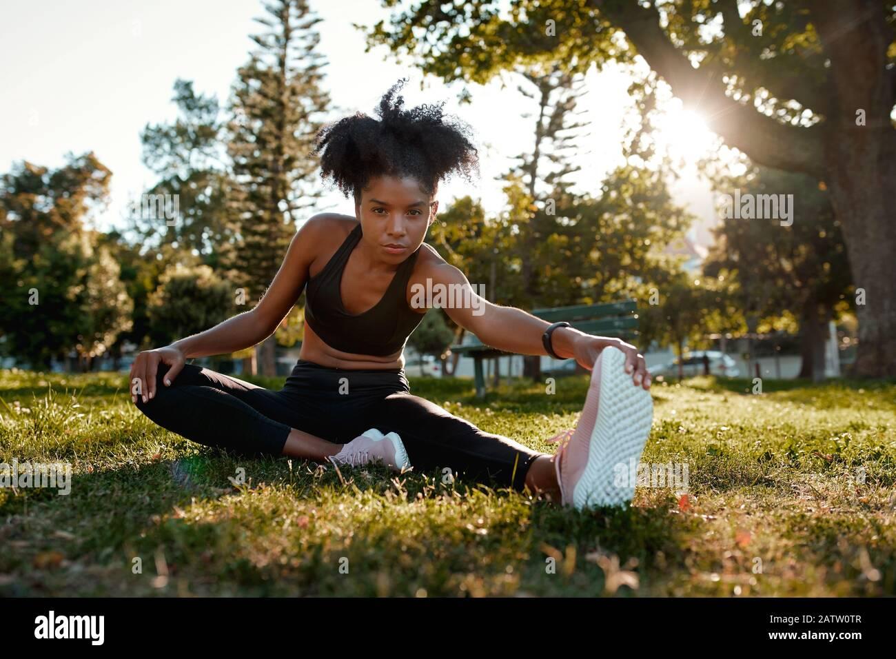 Retrato de una determinada mujer afroamericana sentada en hierba verde haciendo ejercicio en el parque - joven mujer negra calentándola Foto de stock