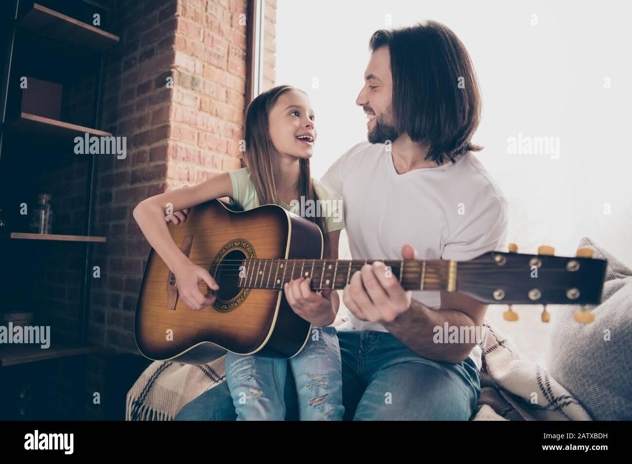Foto de la pequeña adorable dama bonita y su guapo joven papá sentarse ventana bajo los ojos mantener la guitarra acústica aprender nueva canción pasar tiempo Foto de stock