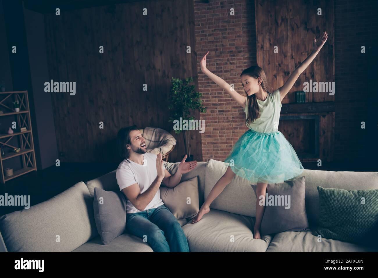Foto de la pequeña dama encantadora muy enérgica guapo mirando a la hija rendimiento de baile de la escuela sentado sofá aplaudiendo los brazos sala de ovación casa Foto de stock