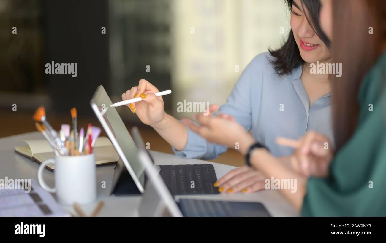 Imagen recortada de un equipo de diseñadores profesionales que consultan su proyecto en una moderna sala de reuniones Foto de stock