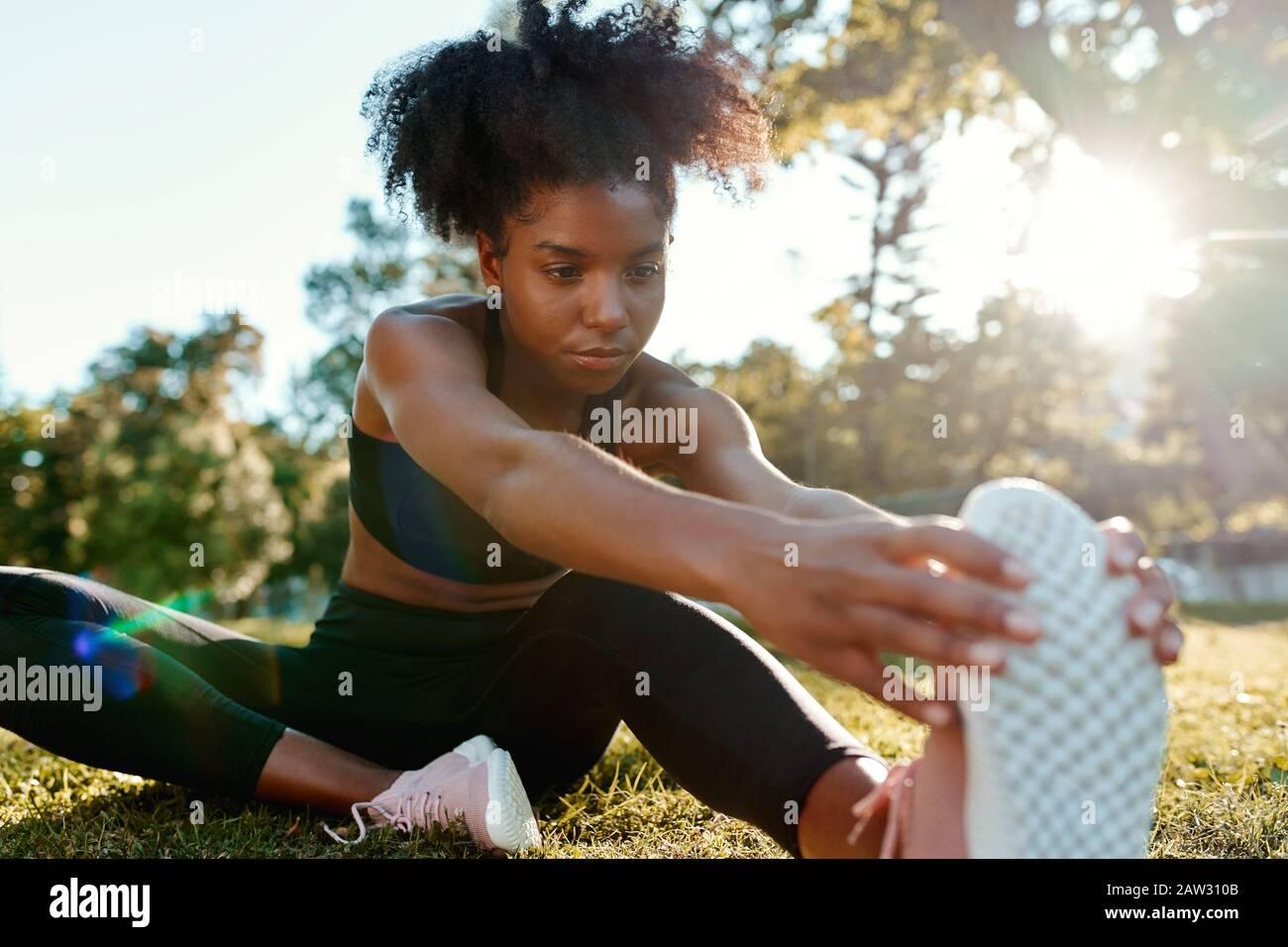 Retrato de una joven afroamericana sentada en el parque estirando sus piernas bajo la luz del sol - joven mujer negra calentando sus piernas antes Foto de stock